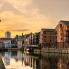 Redeveloped warehouses and modern bridge on the River Aire in Leeds at Sunset