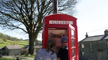 In Settle this year: people look at pictures inside a red telephone box used as a community art gallery - the box was a...