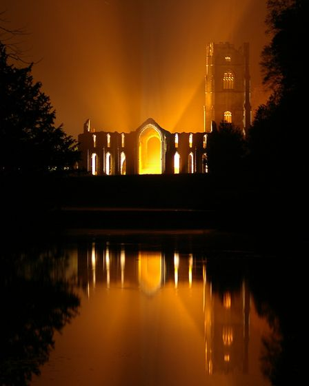 The warm glow of the floodlights of Fountains abbey, North Yorkshire