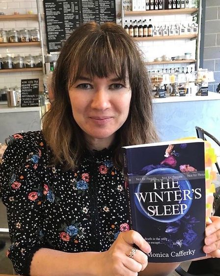 Monica proudly holding a proof copy of her novel