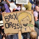 """A protester holds a placard of Boris Johnson with the words """"Brex Orcist"""" outside Downing Street. (Photo by John Keeble/Getty..."""