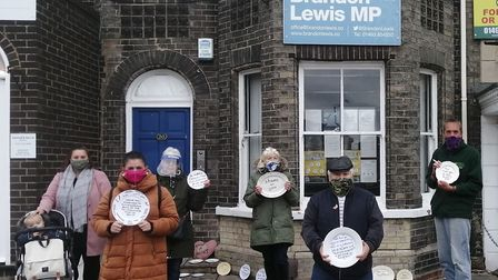 Residents, parents and campaigners gathered outside Mr Lewis's office this morning. The display was