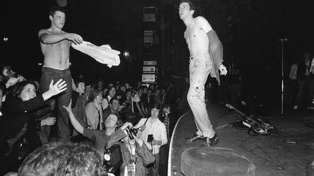 Joe Strummer of The Clash exchanges his shirt with a member of the audience during a concert. (Photo