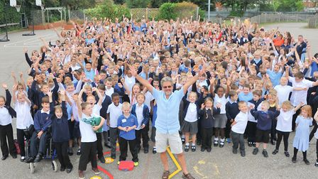 Headteacher Tim Lawes (front centre) and the pupils and staff of Catton Grove Primary celebrate thei