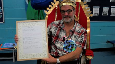 Tim Lawes with framed picture of the lyrics of a new school anthem written to mark him stepping down