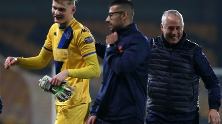 On loan Norwich City goalkeeper celebrates King's Lynn's FA Cup victory over Port Vale with manager