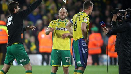Timm Klose pours champagne over Christoph Zimmermann with Teemu Pukki watching on, as Norwich City c