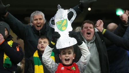 A happy young Norwich fan holds a tinfoil trophy aloft at the end of City's FA Cup fifth round trium