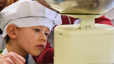 George Amerasekera, four, studies the scales as children learn about making bread, butter and jam at