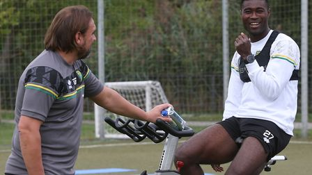 Norwich City head coach Daniel Farke shares a joke with Alex Tettey during pre-season training in Ge