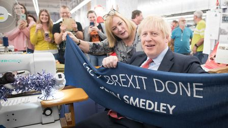 Prime Minister Boris Johnson holds up a banner with the words 'Get Brexit Done' during a visit to the John Smedley Mill
