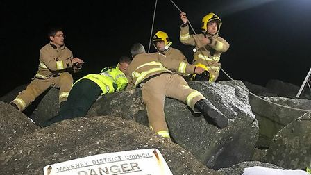 Emergency services rescue a woman trapped beneath the rocks at Ness Point, Lowestoft. Photo: HM Coas