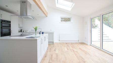Light and airy kitchen with white units including a central island with hob and extractor, double oven and bi-folding...