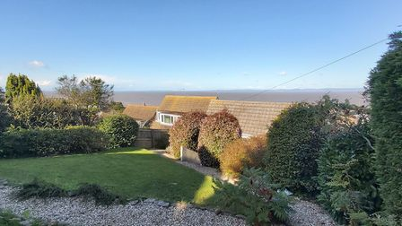 A lawned garden with shrubs and hedges, the back of neighbouring properties and the sea beyond.