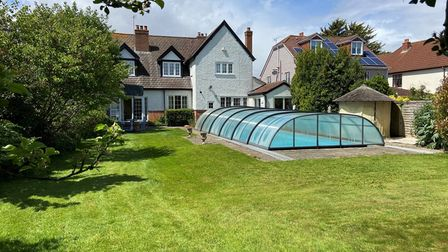 lawn garden pool with cover back of two-storey house trees shrubs shed hut
