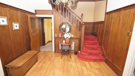 wood-pannelled hallway with shoe store, staircase with left-turn, red carpet and wooden bannister, doorway into room