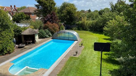 large garden with lawn and blue swimming pool and hut, surrounded by trees and shrubs