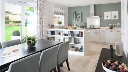 open plan kitchen with shelf unit divider patio doors and a window table and chairs