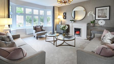 living room with cream fireplace and gas fire with round mirror above, white bay window, beige sofa chairs and walls and a...