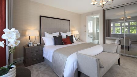 bedroom with beige walls and carpet, king-size bed with chaise long at end, mirrored wardrobes
