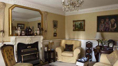 The living room features a French style cast plaster ornate fireplace. The Victorian nursing chair in the foreground is...