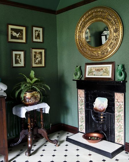 The spacious bathroom, which was converted from a bedroom, boasts its own fireplace set with Dartmouth pottery green...