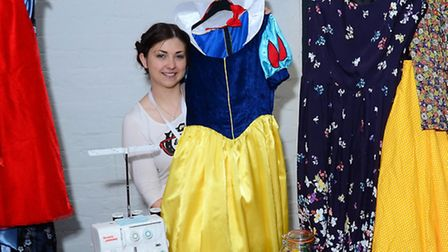 Hannah Howe surrounded by her range of dresses