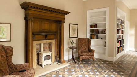 The entrance hall with log burder and original tiled floor Photo: Lucy Arterton
