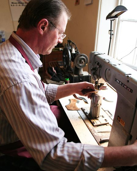 A master craftsman at work stitching on the sewing machine