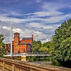 Derby Silk Mill with the needle mast of Cathedral Green footbridge