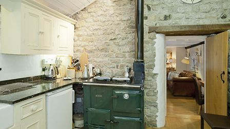 Exposed limestone walls in the cosy country kitchen. 'It's always warm in here by the Aga.' Photo: www.ehouse.co.uk