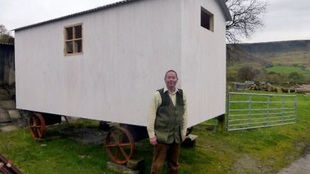 Allan Gagen-Hill with a shepherd's hut that is under construction