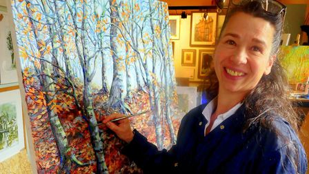 Louise Jannetta putting the finishing touches to a textured painting of a woodland scene