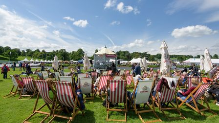 Visitors relax in deck chairs by the piano stage at RHS Chatsworth Flower Show