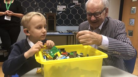 Robert Daunt is shown the Lego by a young pupil