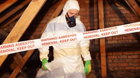 A worker wearing protective clothing while clearing the hazardous substance, asbestos, from an old attic - one of the...