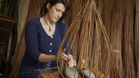 Rachel making a basket in her workshop, surrounded by her raw materials
