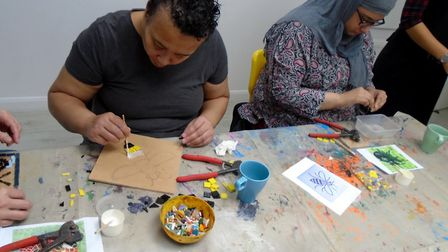Members of a group working on mosaics