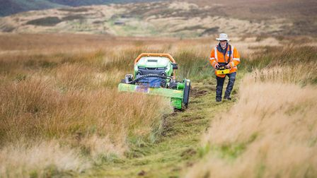 Moors for the Future Partnership conservation officer demonstrates the remote mower in action on the Dark Peak moors