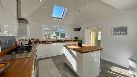 white modern kitchen with central island, white units, velux window above a main window, wooden worktops and gas hob