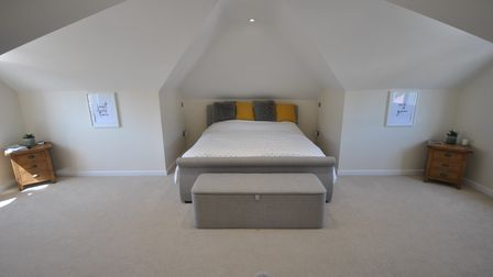 master bedroom with double bed in the middle of an alcove, cream walls and beige carpet