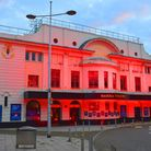 The Marina Theatre in Lowestoft illuminated in red.
