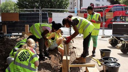 Young people from Berger Primary School and Cardinal Pole Secondary School constructing a community