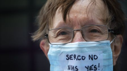 A campaigner outside the Department of Health and Social Care office in London protesting over Serco's handling of the...