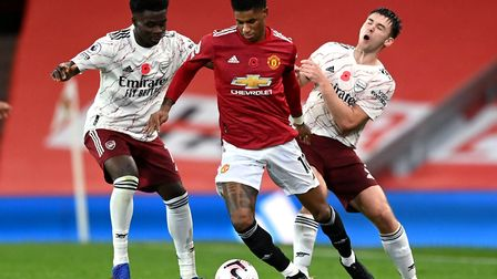 Manchester United's Marcus Rashford (centre) battles for the ball with Arsenal's Kieran Tierney (rig