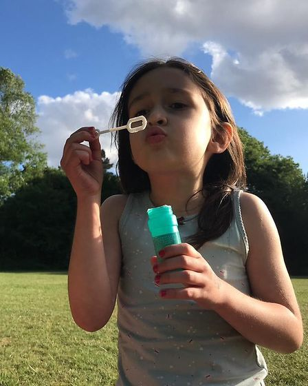 Gabriella Ratcliffe blowing bubbles, while her mum Nazanin remains in Iran under house arrest. Pictu