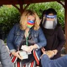 Mora headteacher Kate Bass in the rainbow mask giving out food donated by The Akshaya Patra Foundation