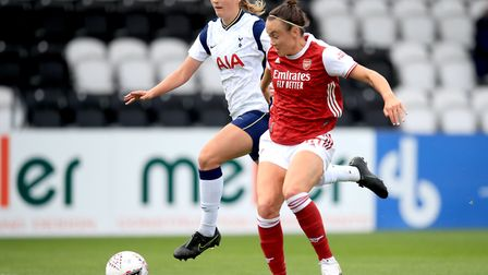 Arsenal's Caitlin Foord (right) battles for the ball with Tottenham Hotspur's Anna Filbey before sco