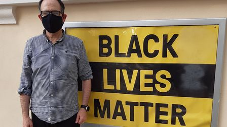 Andy Pakula by the Black Lives Matter banner. Picture: New Unity