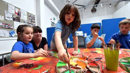 Children at Hampstead Community Centre's after school play centre painting letters for an autumn-themed wall collage.